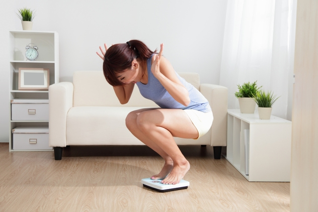 Upset woman on weigh scale at home asian