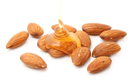 almonds with honey isolated on white