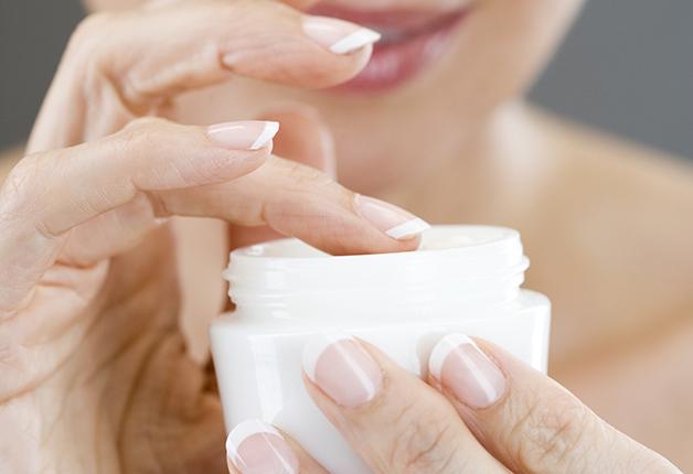 Middle-aged woman applying moisturising cream