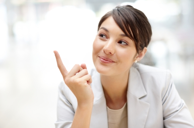 Smart and young female executive pointing at something interesting