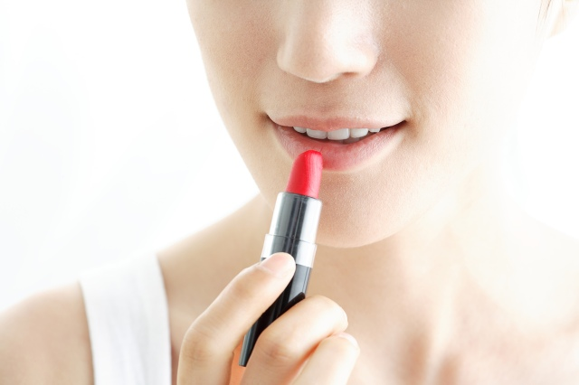 woman applying lipstick,close-up